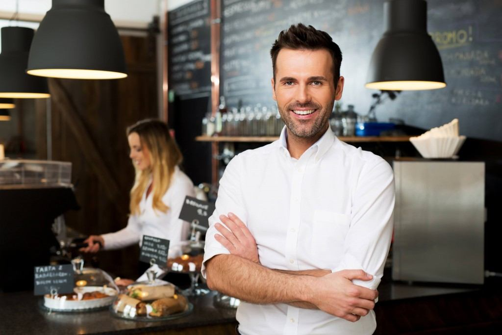 Happy small business owner standing at front of bar with employee in background preparing coffee