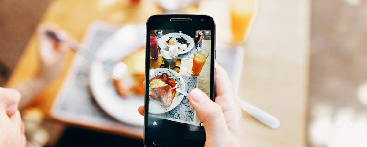 Person Holding Phone Taking Picture of Brunch Order