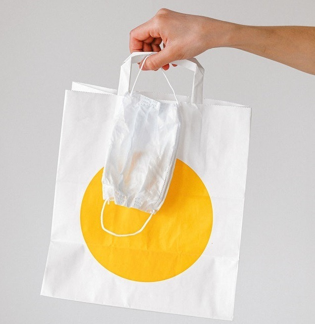 Person Holding Takeout Bag and Face Mask