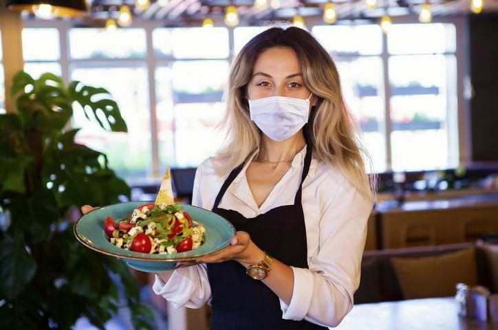 Waitress Wearing a Mask Holding Plate of Food